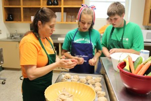 photo of volunteer helping 4-H'ers make pizza dough