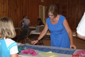 Youth are learning how to measure and cut fabric for their neck coolers with Monica Brinkley, County Extension Director and Agent in Liberty County