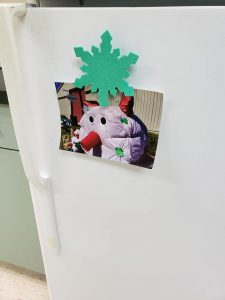 Magnet craft holding a photo on a refrigerator.