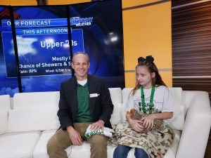 Man and girl on the set of a TV show to promote a 4-H event.