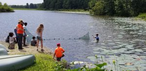 Youth casting a net (seining) in Lake Lafayette for aquatic specimens