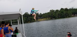 Youth jumping off boat into water