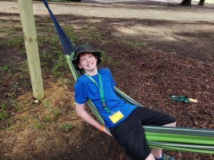 A boy laying in a hammock at camp.