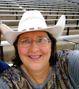 A woman wearing a cowboy hat smiles for the camera