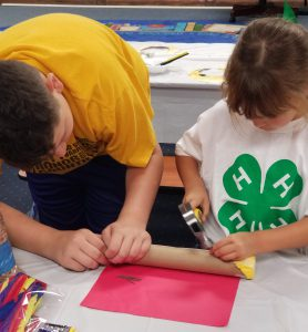 A volunteer is helping a child with a hammering craft project.