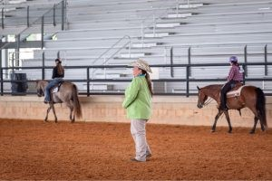 Youth on horses competing in area at horse show.