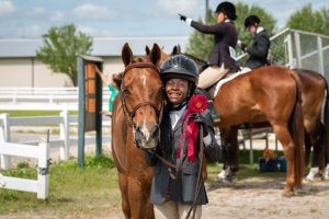 Youth posing with horse at horse show.