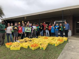 A group of teens pose for a picture behind food collected to be donated