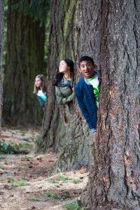 Youth posing, peaking around trees