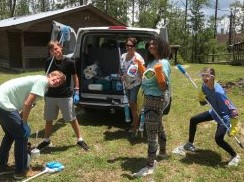 group of youth in funny poses with cleaning supplies