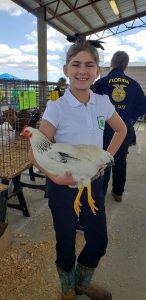 4-H youth posing with her show bird at a show.