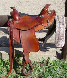 leather saddle sitting on fence