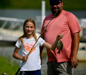 photo of a girl with a fishing pole and fish
