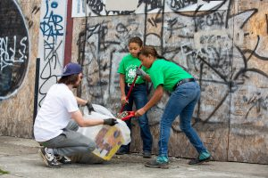 A picture containing 4-H youth and volunteers helping clean up their community.