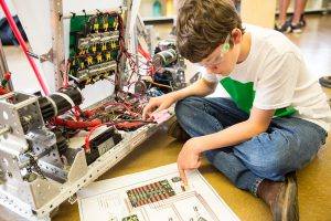 A picture containing a child working on a robot