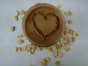 Heart drawn in jar of peanut butter with peanuts surrounding jar
