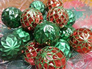 Red and green Christmas tree ornaments in a clear bowl