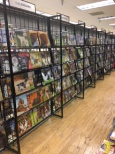 Store aisle with 5-shelf racks of calendars for sale.
