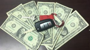 Six one-dollar bills fanned out on a table with a red key chain with a black and silver vehicle key on top of the bills