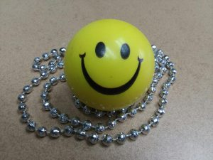 Yellow squishy ball with smiley face surrounded by silver bead necklace