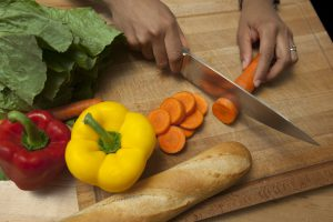 Hands holding knife cutting orange carrot on wooden board with red and yellow peppers, lettuce, and bread