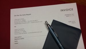Auto repair invoice with checkbook and pen