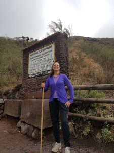 Woman with walking stick wearing purple sweater and black pants on dirt path in front of stone sign and split rail fence