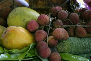 pink, green, yellow tropical fruit with green leaves