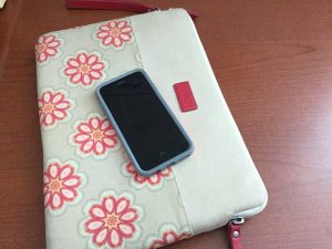 picture of a cell phone on a flowered material case on a woodgrain desk