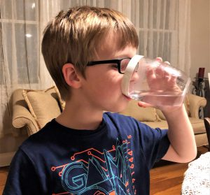 Boy drinking water from clear glass