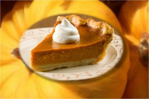 slice of pumpkin pie on plate in front of whole pumpkins