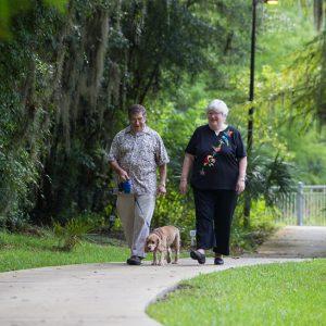 two people walking their dog