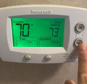 Finger changing temperature on thermostat