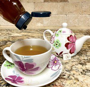 tea pot, tea cup filled with tea, honey bottle
