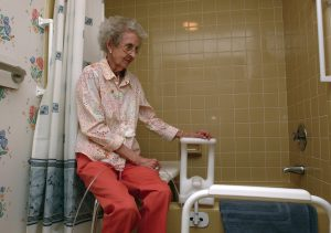 An elderly persons bathroom with grab bars and a shower chair.