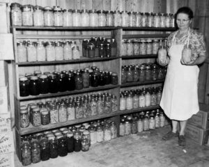 Woman standing in front of shelves of home canned food.