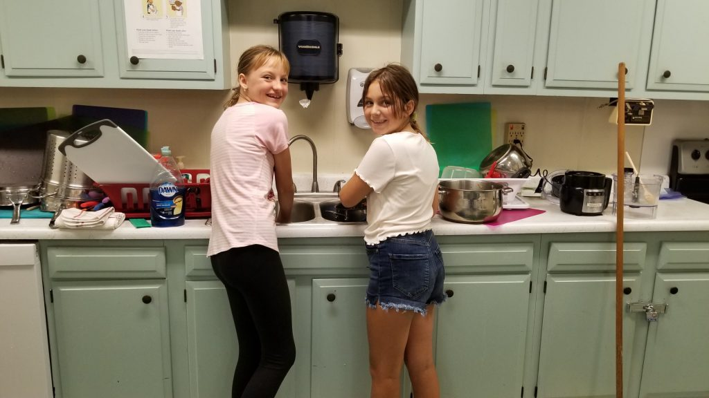 two children washing dishes