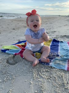 Baby playing in sand at the beach.