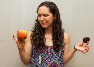 Confused woman choosing between apple and snack cake