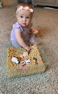 Baby with bin of cereal and toys