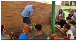 Larry teaching youth about gardening in a school garden