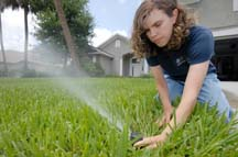 In this photo released from the University of Florida Institute of Food and Agricultural Sciences, extension agent Janet Bargar checks the water flow and direction of a pop-up irrigation system at a home. Bargar, a water quality expert, suggests residents check with their county extension office about local watering restrictions. She says the ideal time to water is before sunrise and that residents should check irrigation systems watering the sidewalk. (AP photo/University of Florida/Josh Wickham)