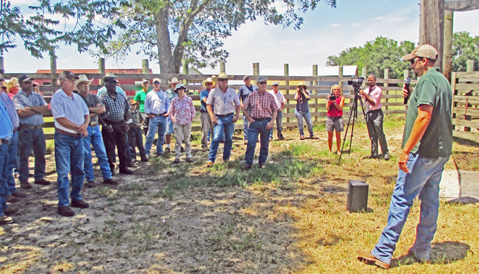 Lee Bigham showed the tour group how the hydralica chute and sorting gates worked in their cowpens.