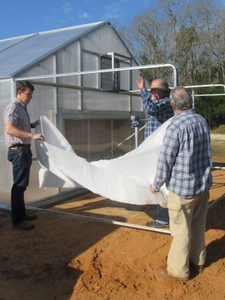 Insect screening being installed on screen structure around a greenhouse cooling pad.