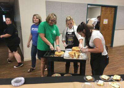 Faculty cutting cake